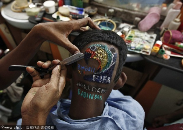 Indian hairstylist Das cuts hair of soccer fan inside saloon on the outskirts of Kolkata